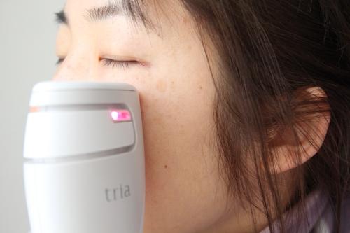 トリア・スキン エイジングケアレーザーを顔に当て美顔器を起動させる